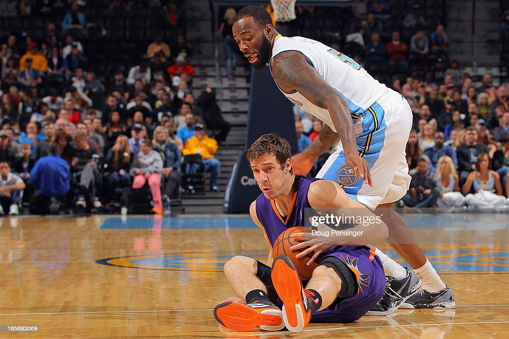 Goran Dragic #1 of the Phoenix Suns goes to the court to control a loose ball against Damion James #5 of the Denver Nuggets during preseason action at Pepsi Center on October 23, 2013 in Denver, Colorado. The Suns defeated the Nuggets 98-79.