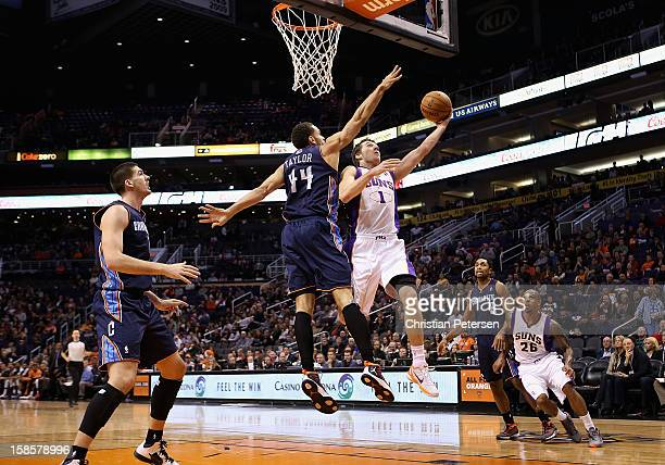 Goran Dragic of the Phoenix Suns lays up a shot past Jeffery Taylor of the Charlotte Bobcats during the NBA game at US Airways Center on December 19...