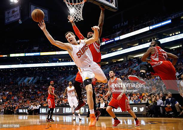 Goran Dragic of the Phoenix Suns makes a leaping pass ahead of Josh Smith of the Houston Rockets during the second half of the NBA game at US Airways...