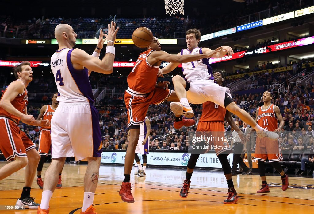 <a gi-track='captionPersonalityLinkClicked' href=/galleries/search?phrase=Goran+Dragic&family=editorial&specificpeople=4452965 ng-click='$event.stopPropagation()'>Goran Dragic</a> #1 of the Phoenix Suns passes the ball around John Henson #31 of the Milwaukee Bucks to <a gi-track='captionPersonalityLinkClicked' href=/galleries/search?phrase=Marcin+Gortat&family=editorial&specificpeople=589986 ng-click='$event.stopPropagation()'>Marcin Gortat</a> #4 during the NBA game at US Airways Center on January 17, 2013 in Phoenix, Arizona. The Bucks defeated the Suns 98-94.
