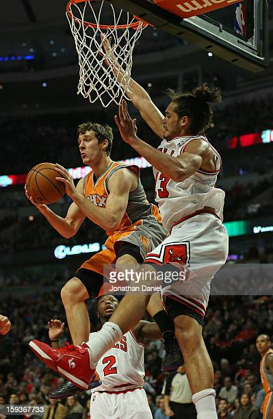 Goran Dragic of the Phoenix Suns puts leaps to pass under pressure from Joakim Noah and Nate Robinson of the Chicago Bulls at the United Center on...