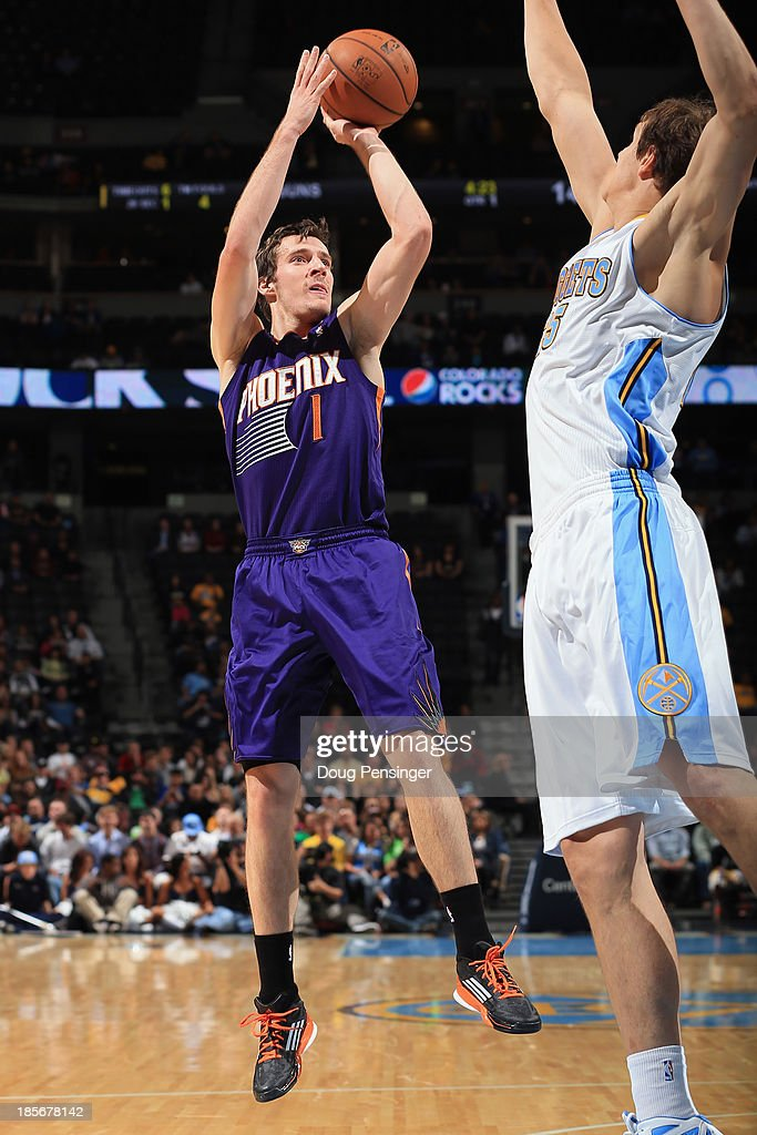 Goran Dragic #1 of the Phoenix Suns takes a shot over Timofey Mozgov #25 of the Denver Nuggets during preseason action at Pepsi Center on October 23, 2013 in Denver, Colorado.