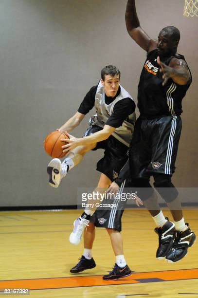 Goran Dragic passes around Shaquille O'Neal of the Phoenix Suns during NBA TV's Real Training Camp visit to the Phoenix Suns on October 7 at US...