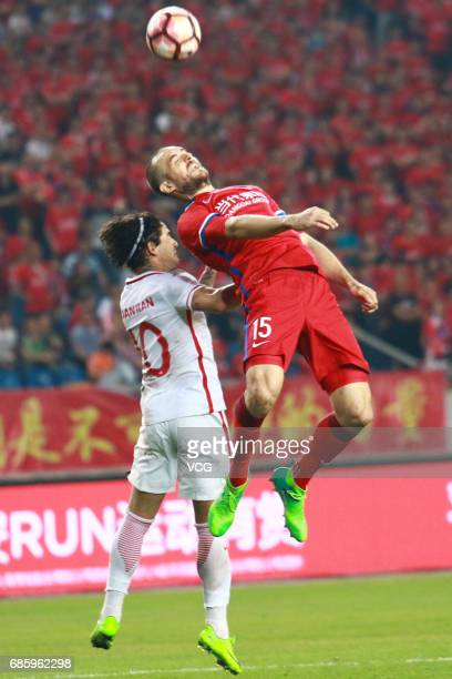 Goran Milovic of Chongqing Lifan and Alexandre Pato of Tianjin Quanjian compete for the ball during the 10th round match of 2017 Chinese Football...