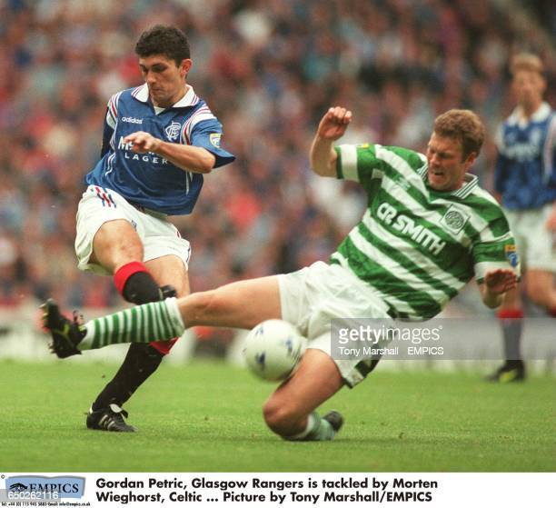 Gordan Petric Glasgow Rangers is tackled by Morten Wieghorst Celtic