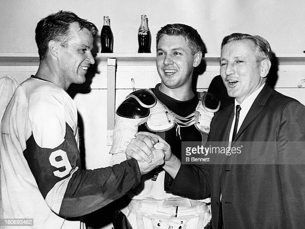 Gordie Howe and Alex Delvecchio of the Detroit Red Wings celebrate in the locker room with head coach Sid Abel after defeating the Chicago Blackhawks...