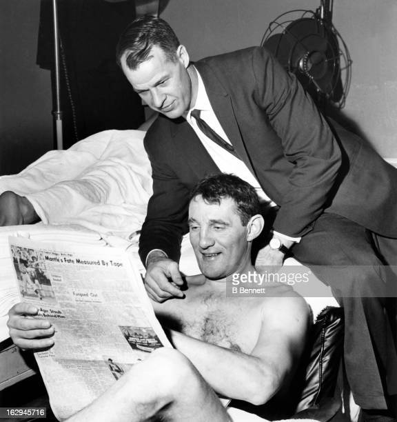 Gordie Howe and Bill Gadsby of the Detroit Red Wings read a newspaper story about Howe and a fan who alleges that Howe punched him in the mouth after...