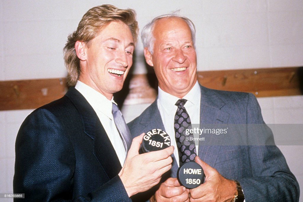 Gordie Howe and Wayne Gretzky of the Los Angeles Kings hold pucks with the number of career points after Gretzky broke Howe's career points record...