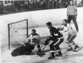 Gordie Howe of the Detroit Red Wings flips the puck into the net past goalie Johnny Bower of the Toronto Maple Leafs while evading a check by Larry...