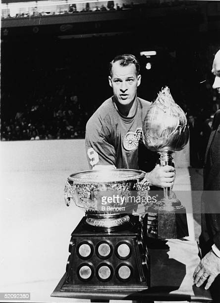 Gordie Howe of the Detroit Red Wings poses on the ice with the Art Ross and Hart trophies 1960s The Art Ross Trophy is to the top NHL point earner in...