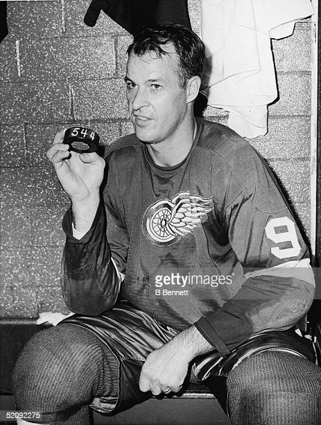 Gordie Howe of the Detroit Red Wings sits in the locker room and holds a hockey puck numbered 544 on October 24 1963 at the Detroit Olympia Stadium...