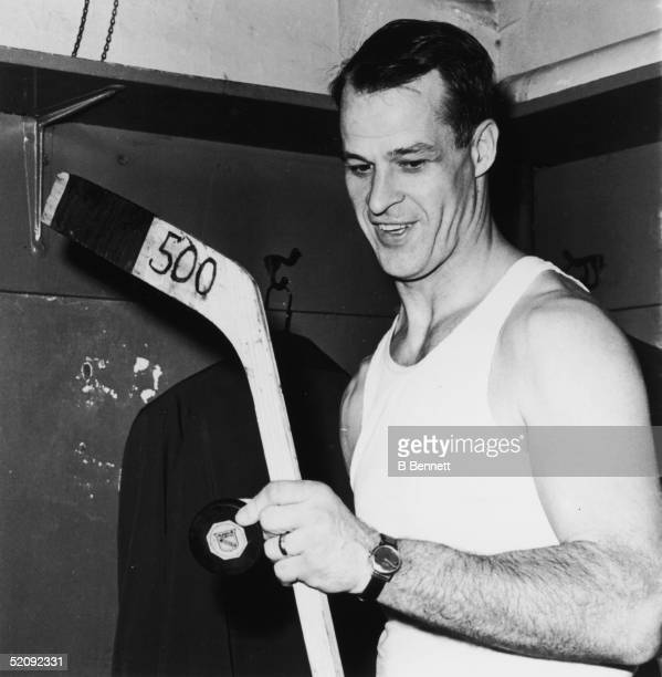 Gordie Howe of the Detroit Red Wings stands in a locker room in his undershirt as he holds a hockey puck and stick labeled 500 in honor of his 500th...