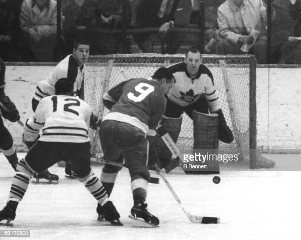 Gordie Howe of the Detroit Red Wings tries to control the bouncing puck in front of goalie Johnny Bower of the Toronto Maple Leafs as Ron Stewart of...