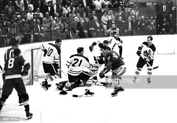 Gordie Howe of the Detroit Red Wings tries to score as he is defended by goalie Johnny Bower George Armstrong Bob Baun and Allan Stanley of the...