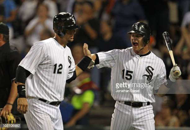 Gordon Beckham of the Chicago White Sox congratulates teammate AJ Pierzynski after Pierzynski hit a sacrifice fly to socre a run against the Seattle...
