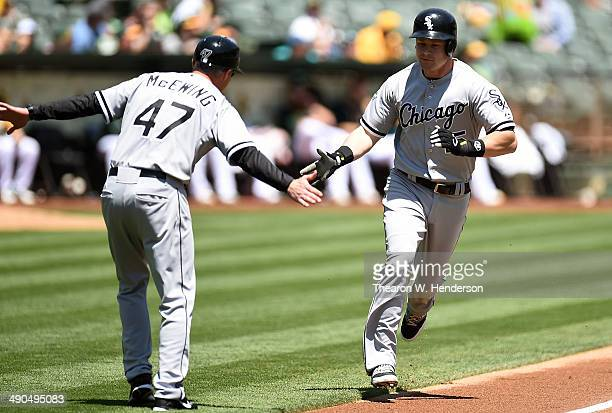 Gordon Beckham of the Chicago White Sox is Congratulated by third base coach Joe McEwing after Beckham hit a leadoff home run in the top of the first...