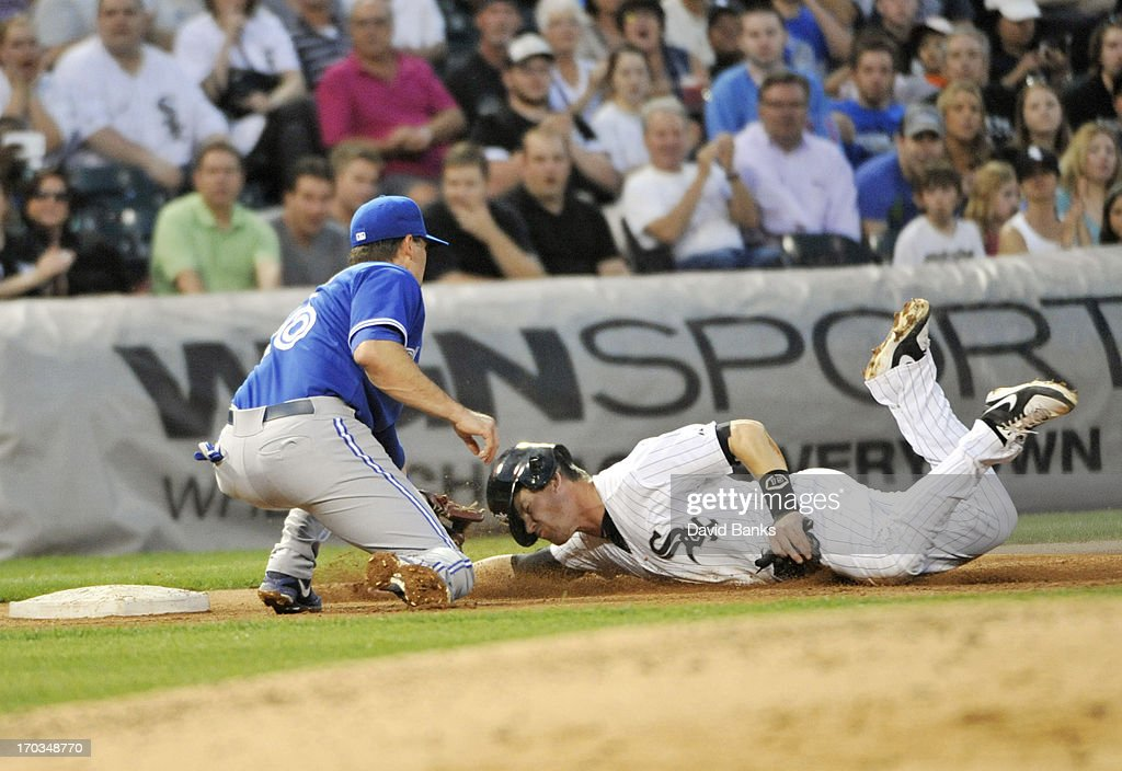 Gordon Beckham #15 of the Chicago White Sox is tagged out at third base by Mark DeRosa #16 of the Toronto Blue Jays during the fourth inning on June 11, 2013 at U.S. Cellular Field in Chicago, Illinois.