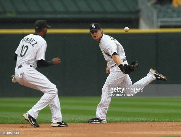 Gordon Beckham of the Chicago White Sox makes a backhanded flip of the ball to Alexei Ramirez in an attempt to retire a the Detroit Tiger runner at...