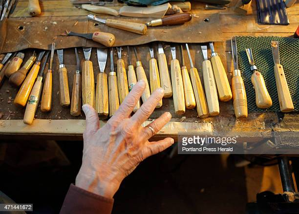 Gordon Bok's hand hovers over wood carving tools as he contemplates which one to use on a relief carving of a herring boat he is working on in his...
