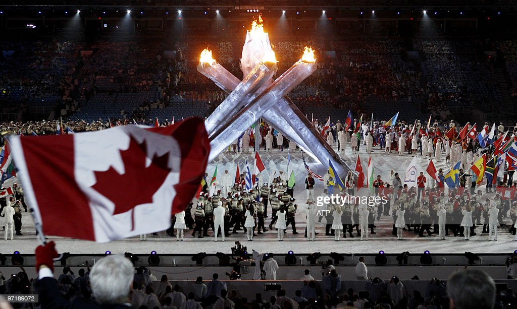 Gordon Campbell (L), the Premier of British Columbia, waves a Canadian flag during the closing ceremony of the Vancouver 2010 Winter Olympics, February 28, 2010.
