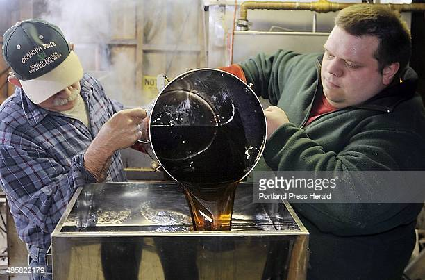 Gordon Chibroski/Staff Photographer Steven McKenney and son Ben McKenney pour condensed maple syrup into the canning machine that will reheat filter...