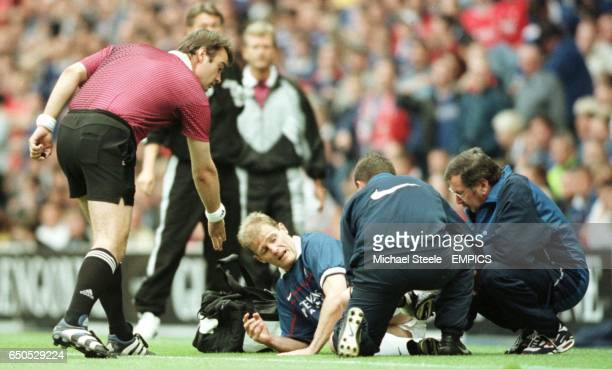 Gordon Durie of Rangers lies injured as referee Kim Milton Nielsen has a word with him as he is being treated