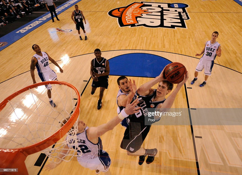 Gordon Hayward of the Butler Bulldogs drives for a shot attempt against Kyle Singler and Brian Zoubek of the Duke Blue Devils during the 2010 NCAA...