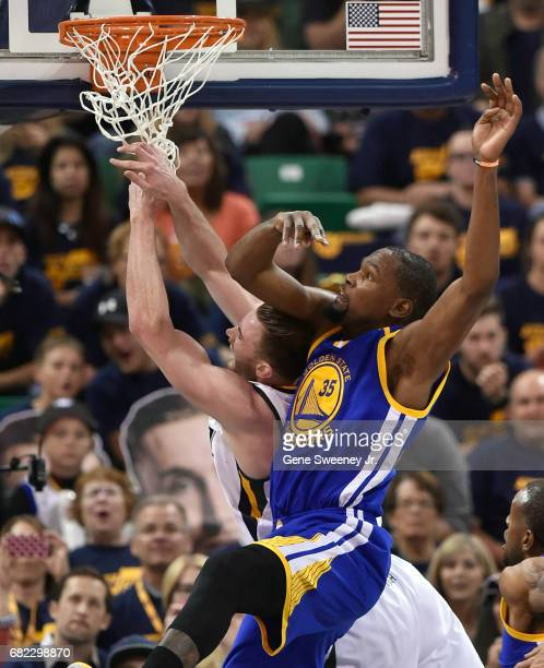 Gordon Hayward of the Utah Jazz collides under the basket with Kevin Durant of the Golden State Warriors in Game Three of the Western Conference...