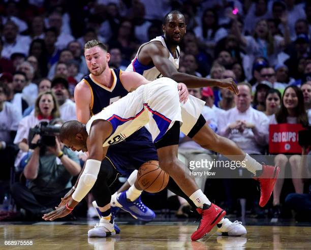 Gordon Hayward of the Utah Jazz collides with Chris Paul of the LA Clippers as he loses the ball as Luc Mbah a Moute looks on during the first half...
