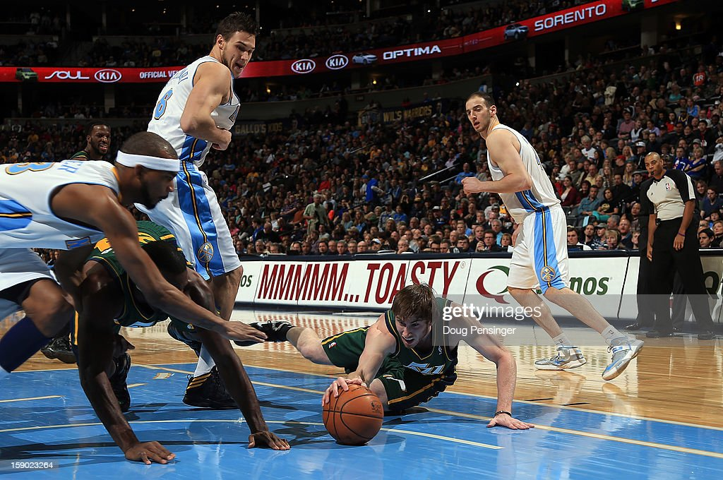 Gordon Hayward #20 of the Utah Jazz dives for and controls a loose ball against the Denver Nuggets at the Pepsi Center on January 5, 2013 in Denver, Colorado. The Nuggets defeated the Jazz 110-91.