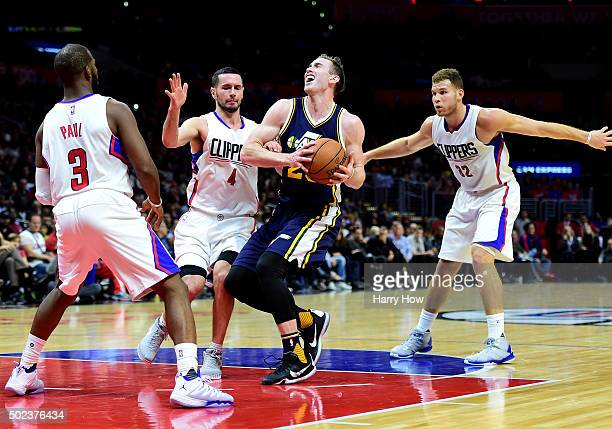 Gordon Hayward of the Utah Jazz drives on Chris Paul JJ Redick and Blake Griffin of the Los Angeles Clippers at Staples Center on November 25 2015 in...