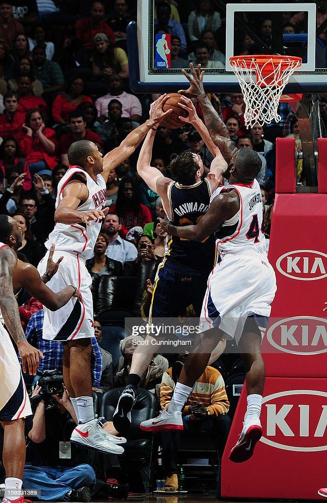 Gordon Hayward #20 of the Utah Jazz gets rejected against Ivan Johnson #44 of the Atlanta Hawks on January 11, 2013 at Philips Arena in Atlanta, Georgia.