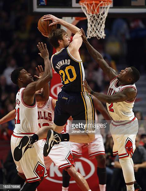 Gordon Hayward of the Utah Jazz leaps to pass between Jimmy Butler and Nate Robinson of the Chicago Bulls at the United Center on March 8 2013 in...