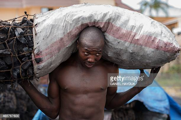 Gordon William carries a sack of traditional charcoal at a charcoal depot in Dar es Salaam on March 10 2015 ARTI Energy is a Tanzanian company...