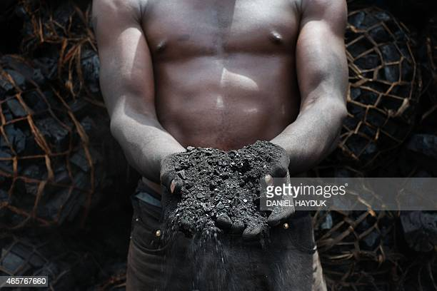 Gordon William shows discarded char powder at a charcoal depot in Dar es Salaam on March 10 2015 ARTI Energy is a Tanzanian company providing clean...