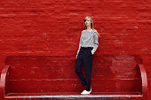 Beautiful model posing against red wall, portrait