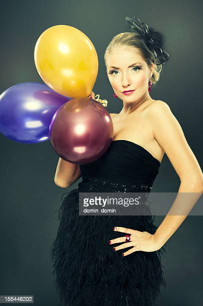 Gorgeous blond young woman in evening dress with baloons, posing