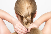 Gorgeous blonde woman braids her hair from behind