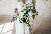 Gorgeous bouquet of white and pink flowers in the hands of the charming bride in a white dress. Artwork. Indoors