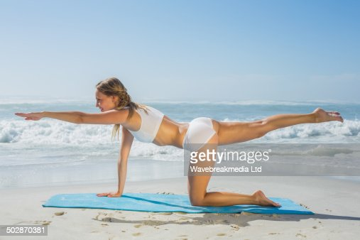 Gorgeous fit blonde in pilates pose on the beach : Stock Photo