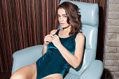 sensual attractive young caucasian woman in lingerie sitting in vintage leather chair