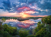 Gorgeous scene with river, green trees, rocks and amazing blue sky with colorful clouds reflected in water at sunset. Fantastic summer landscape with lake, overcast sky and yellow sun in the evening