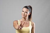 Gorgeous sporty young female portrait showing two finger peace hand sign over gray studio background.