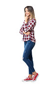 Gorgeous street style woman wearing jeans, plaid shirt and sneakers smiling looking down. Full body length portrait isolated over white studio background.