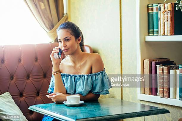 gorgeous woman talking on the phone in a nice bar