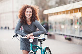 Pretty young woman with bicycle in a city street
