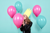 Gorgeous young woman in leather jacket and party hat kissing colourful balloon, isolated over pastel blue coloured background. Birthday Party concept.