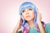 Modern pretty young woman with pastel pink and blue hair and makeup, listening to music on headphones, posing, looking up, wearing pastel green sweater. Pink background, retouched, studio lighting.