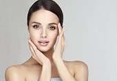 Gorgeous, young, brown haired woman with clean fresh skin is touching the face.  Light smile on the perfect face. Facial treatment, cosmetology, beauty technologies and spa.