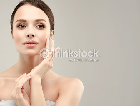 Gorgeous, young woman with clean, fresh skin is touching own face. Cosmetology. : Stock Photo